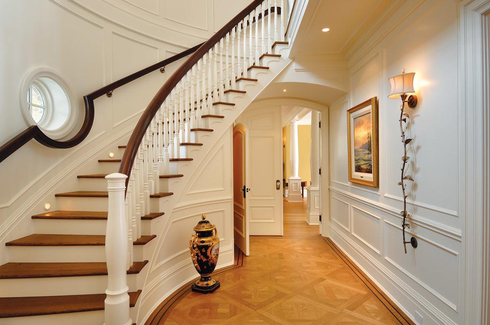 前門門廳的牆壁鑲嵌有白色的裝飾板,手工打造的棕色桃花心木扶手蜿蜒而上。