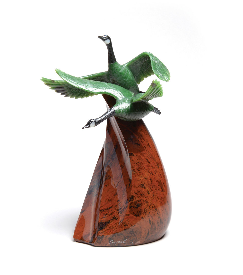 加拿大最具代表性的鳥類رر加拿大大雁,被Lyle Sopel巧妙地運用玉石天然的綠色、黑色和白色呈現出來,彷彿要從棕色的山坡上振翅飛翔。