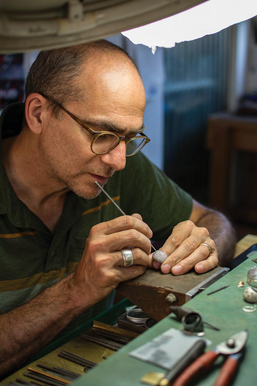 Roberto Fioravanti正在修整他手工打造的金屬珠寶。Photo by Michel Irvine