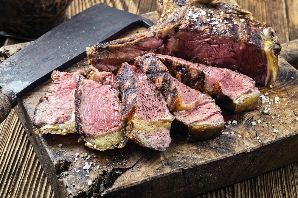 厚厚的佛羅倫薩大牛排整塊的放在架子上燒烤,在上桌前會撒上鹽和橄欖油簡單調味。hlphoto / Shutterstock.com