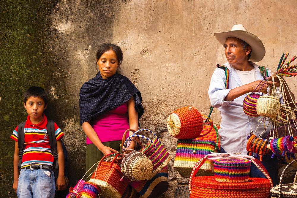 一家人正在集市中販賣色彩艷麗的手工草編製品。