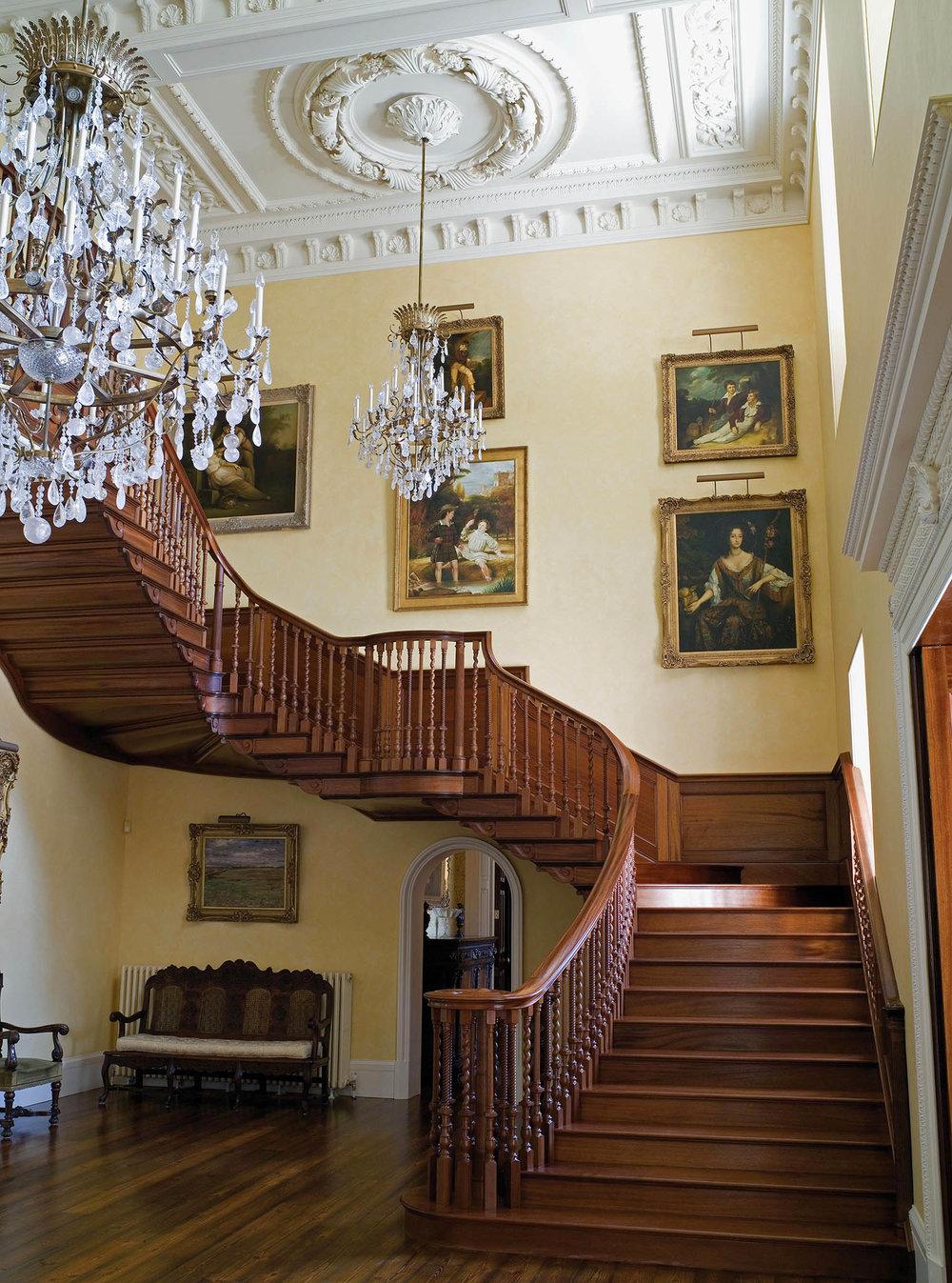 祖先們的肖像畫懸掛在樓梯的轉折處,俯瞰著典雅華麗的門廳。Photo courtesy of Spencer-Churchill Designs Ltd, T/A Woodstock Designs