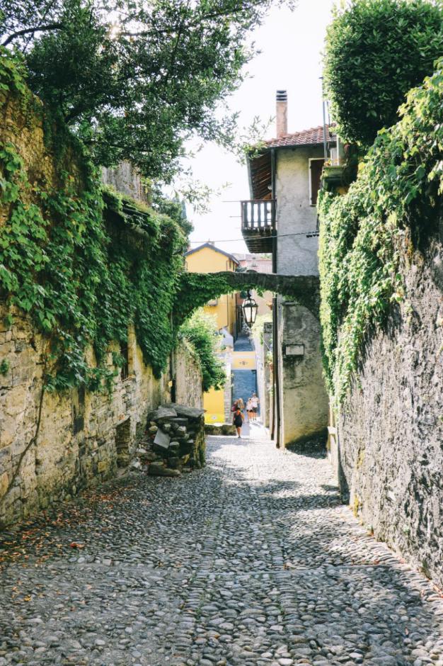 狹窄的鵝卵石街道通往科莫湖畔。路兩邊是中世紀的建築。Mikadun / Shutterstock.com