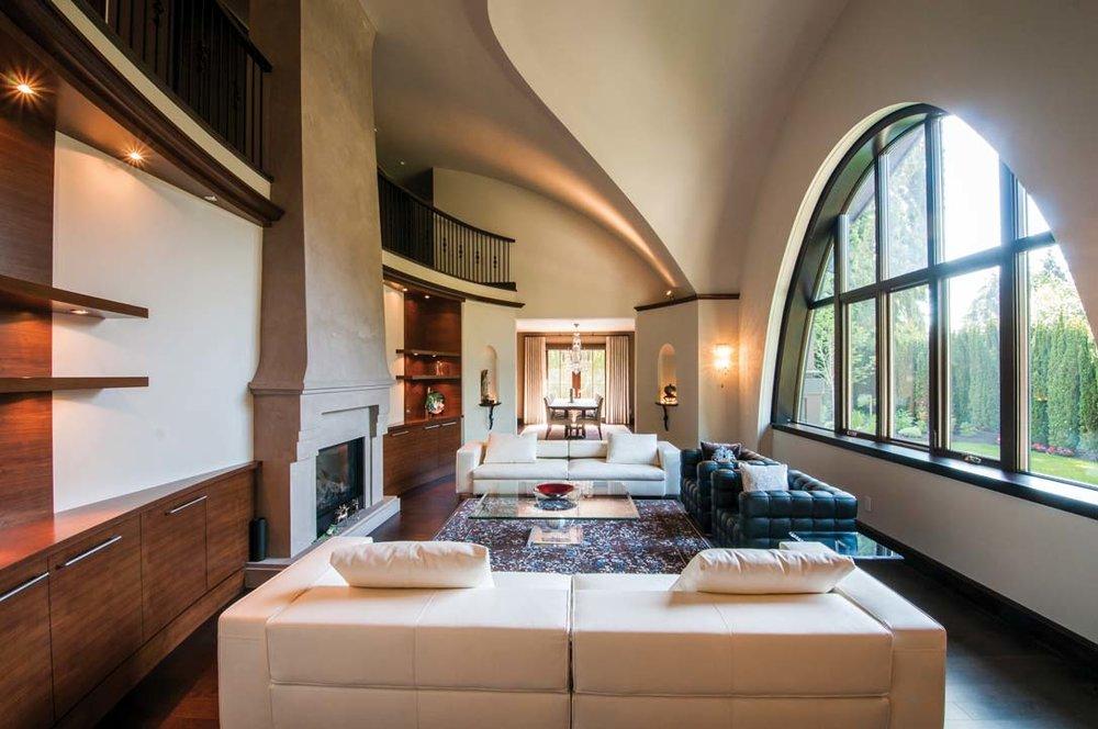 客廳裏壁爐簡潔質樸,天花板的拱形曲線與半圓形的巨大窗戶相互呼應,為空間帶來戲劇化的起伏變幻。