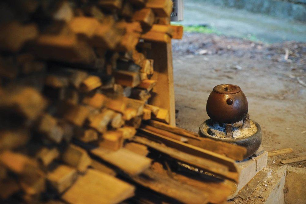 田承泰和妻子一起搭建 「夫妻窯」,燒窯時,添柴口前會放置一壺熱茶湯,用來補充水份。 Photo by Ady Zhuang