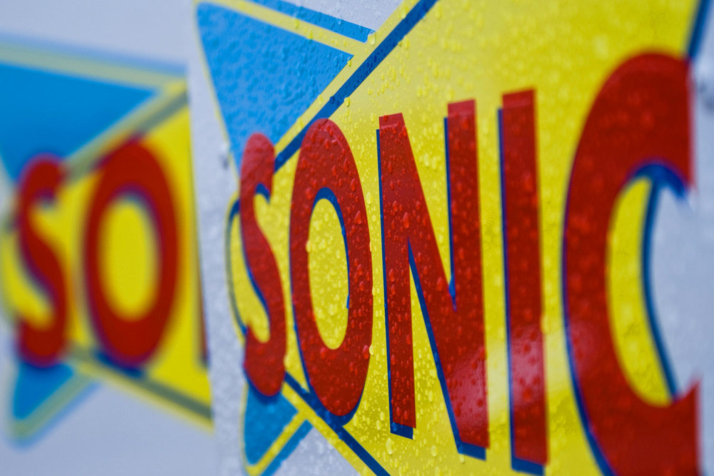 Close-up of sonic sign, in rain