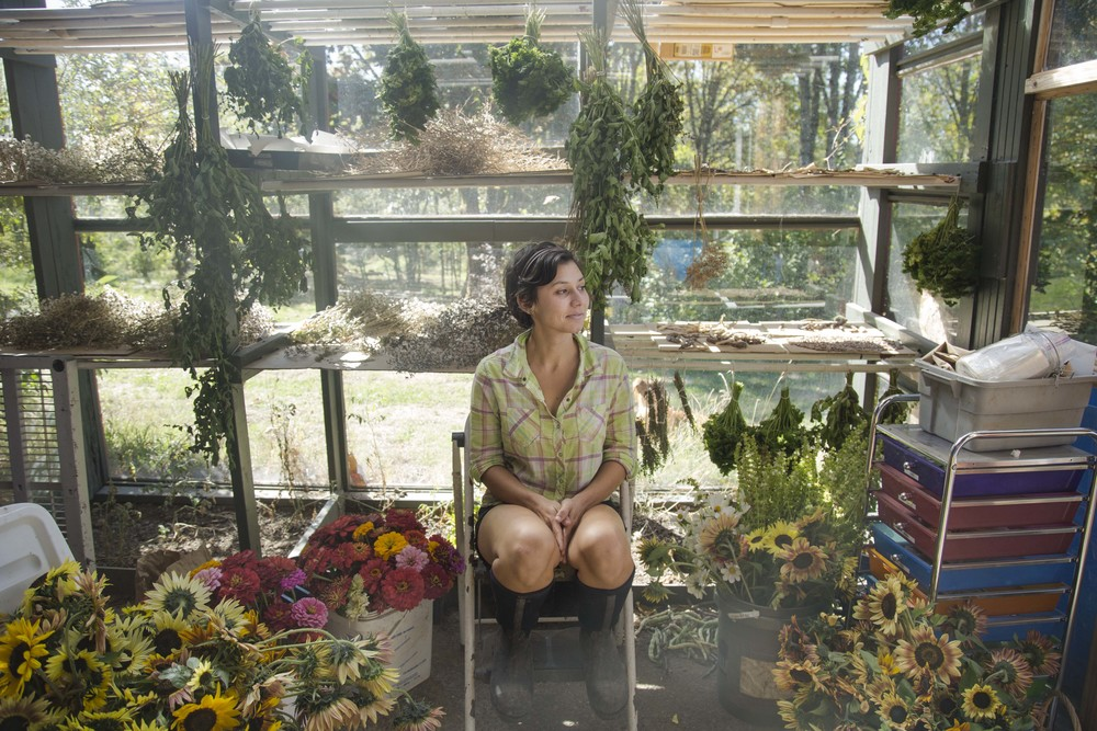 Israelle taking a rest in the greenhouse filled with the morning flower harvest, bundels of herbs for winter and seeds to dry for next season. (Oregon)