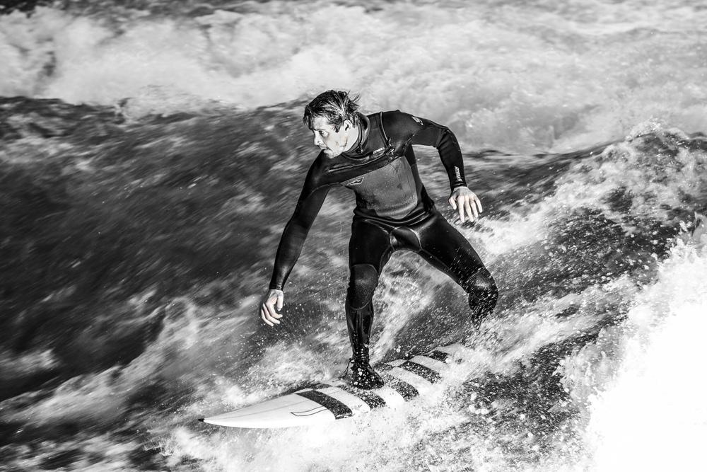 surfers surfing on eisbach river munich