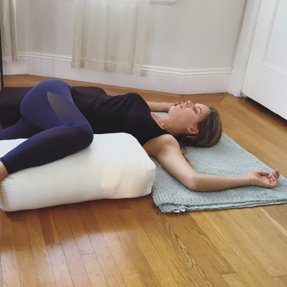 Restorative Twist with bolster for grounding and relaxation.