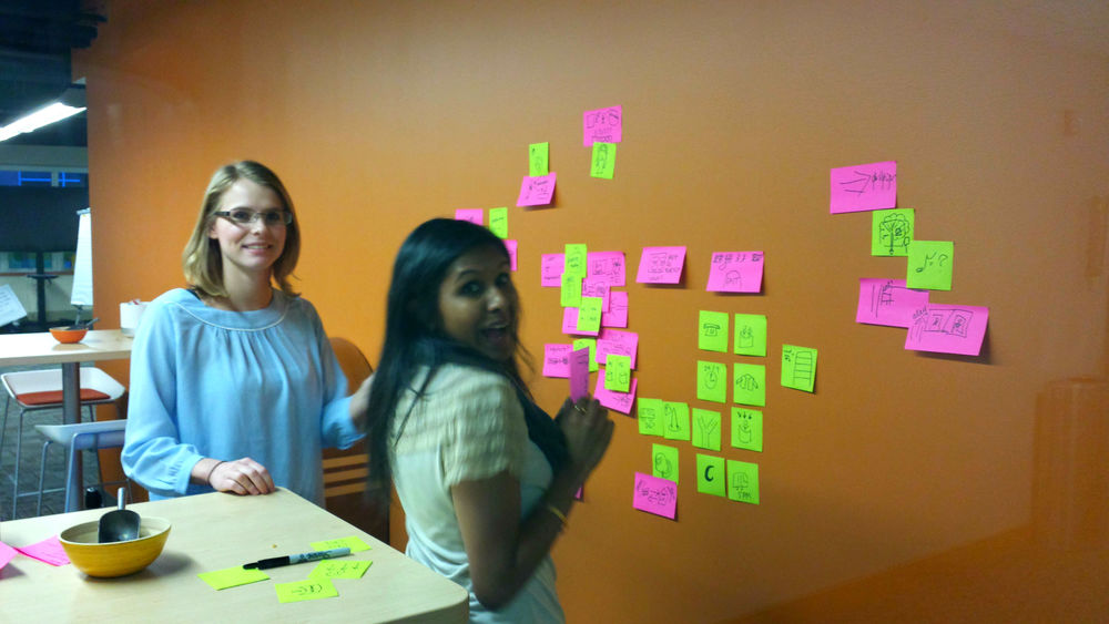 Brandie Carey, left, and Shelly Bhowmik use some wall space to tackle a design challenge.