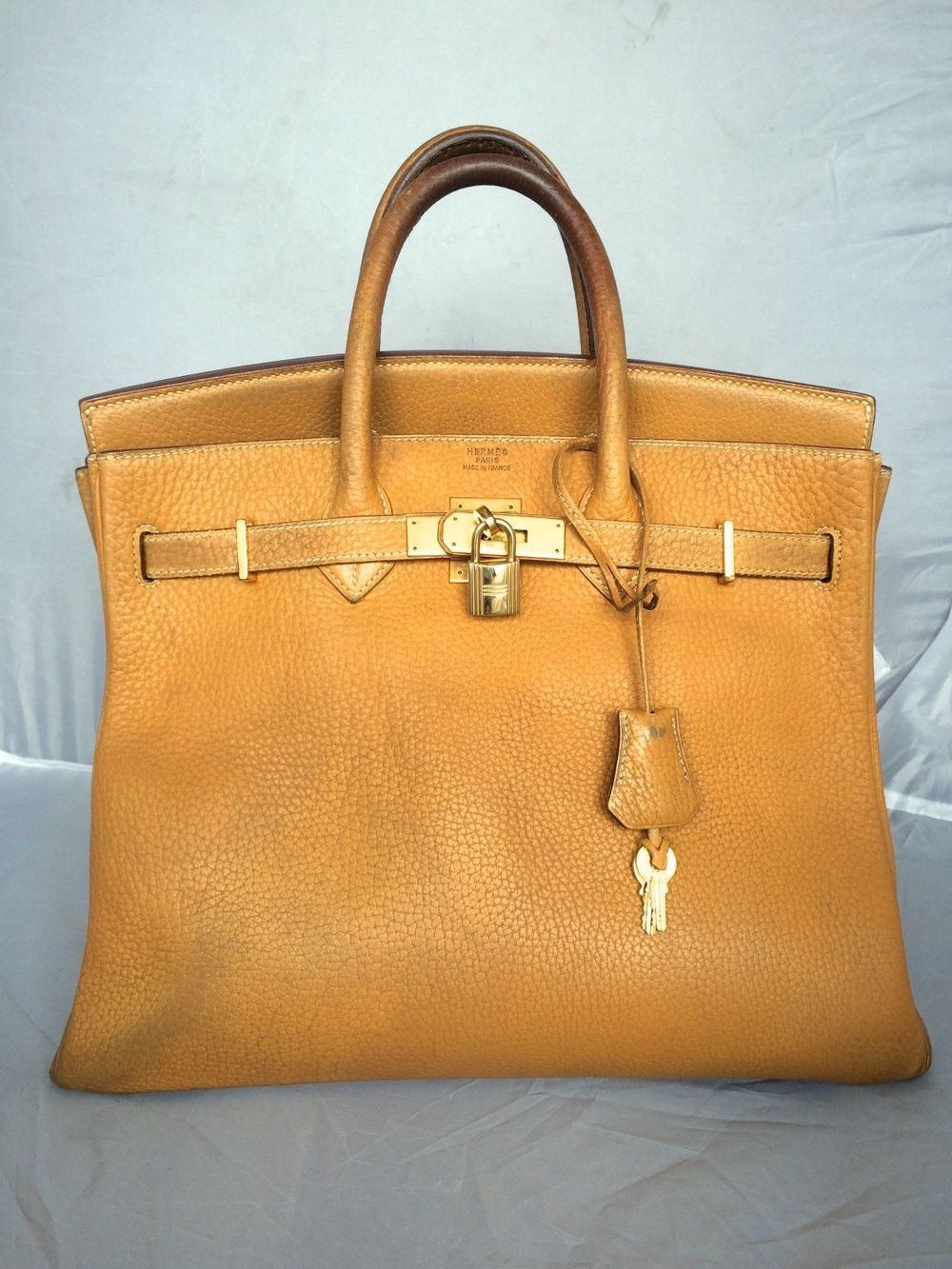 Discolorations in the handles of a Hermes bag.