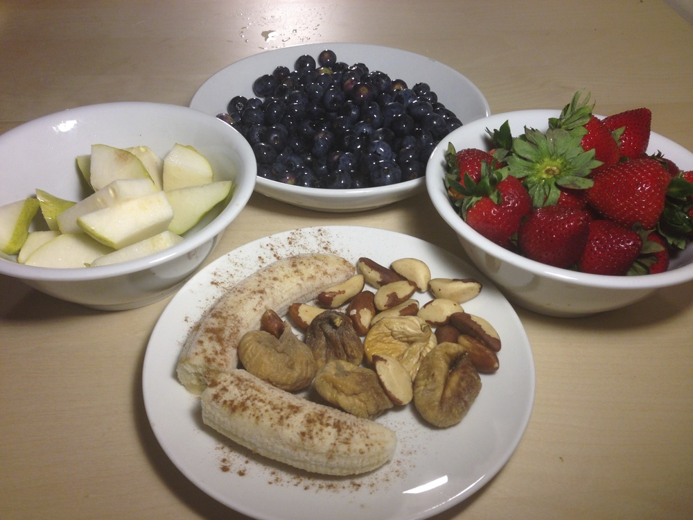 An assortment of healthy dessert: frozen banana, dried figs, Brazil nuts, strawberries, blueberries, and sliced pear.