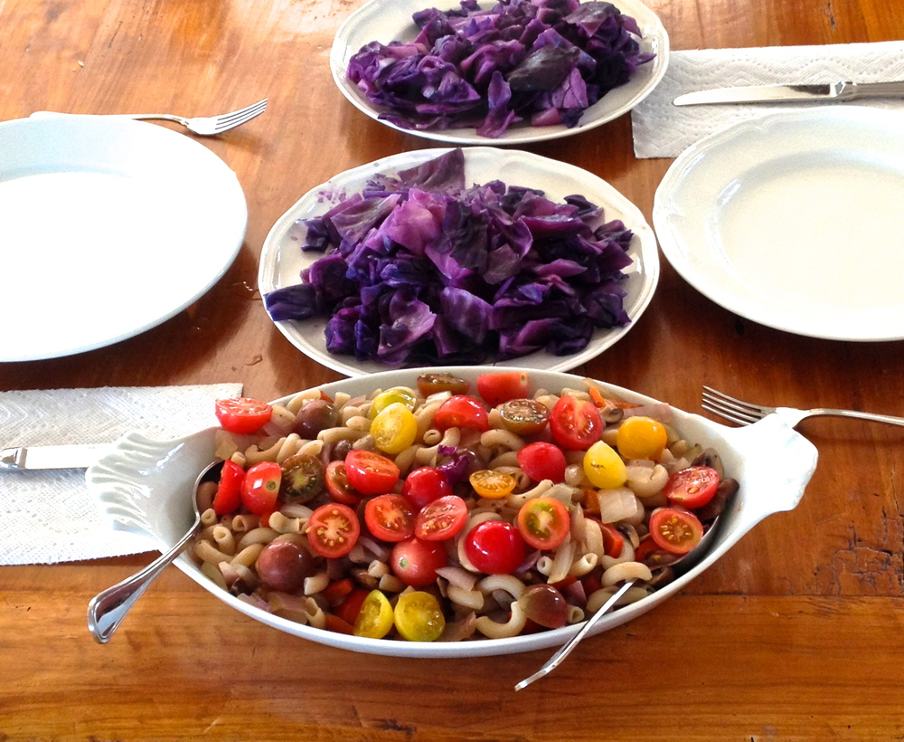 A gourmet lunch of steamed red cabbage with rice pasta, topped with chopped red onion, olive oil, and cherry tomatoes.