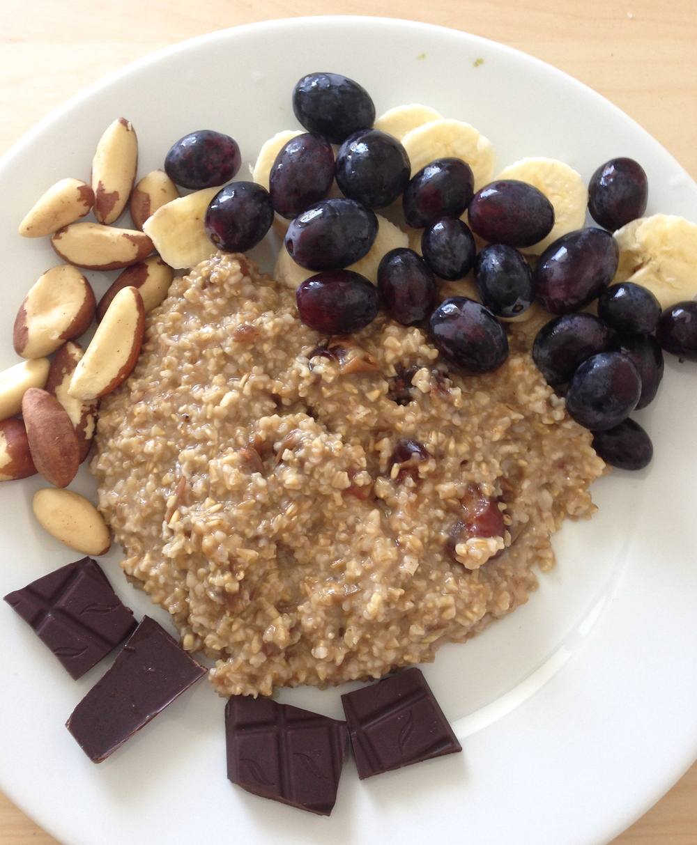 A healthy breakfast plate of steel-cut oatmeal (with dates cooked inside), 85% dark chocolate, grapes, Brazil nuts, and sliced banana.