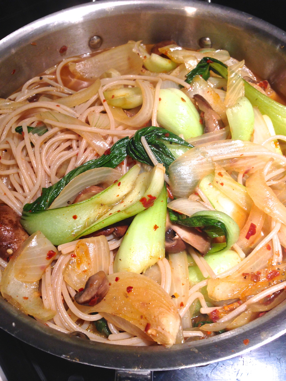 A spicy brown rice pasta soup with onions, mushroom, and bok choy.