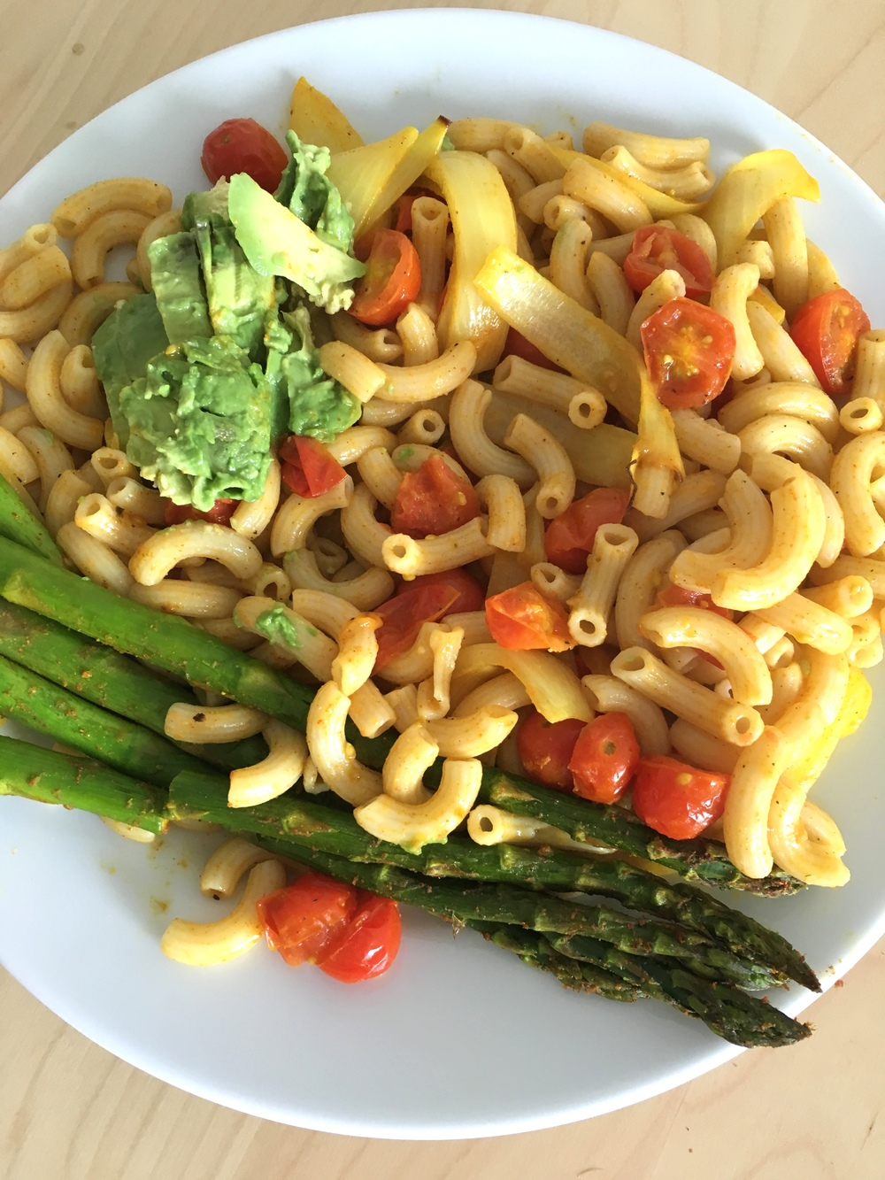 A home-cooked plate of brown rice pasta with sauteed cherry tomatoes and onions, avocado, and roasted asparagus added.