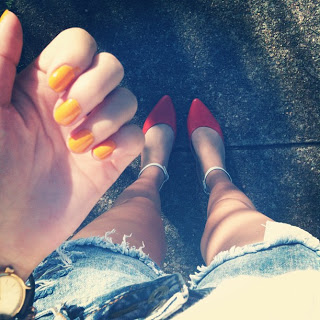 Man repelling in denim cutoffs and tangerine nails