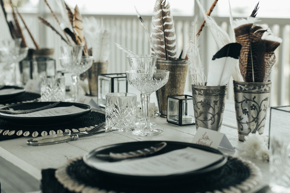 Monochrome - Monochrome can look absolutely striking and adding deep colourful florals against this look will really pop. We created this look using our black plates, boho charger plates with shell details and crystal cut glassware to keep the table looking formal and sophisticated. We've added feathers for some unique texture giving it a boho vibe.