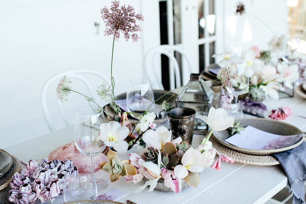 Barnacles & Crystals - The hints of pink and purple pastels in the florals and decor against the white tables keep the feeling soft and romantic. The added rose quartz which symbolises the 'crystal of love' and barnacle clusters combined give off a luxe ocean vibe which radiates love! The feminine pastel florals and succulents by local florist, Bower Botanicals add to the unique styling of the seascape feel.