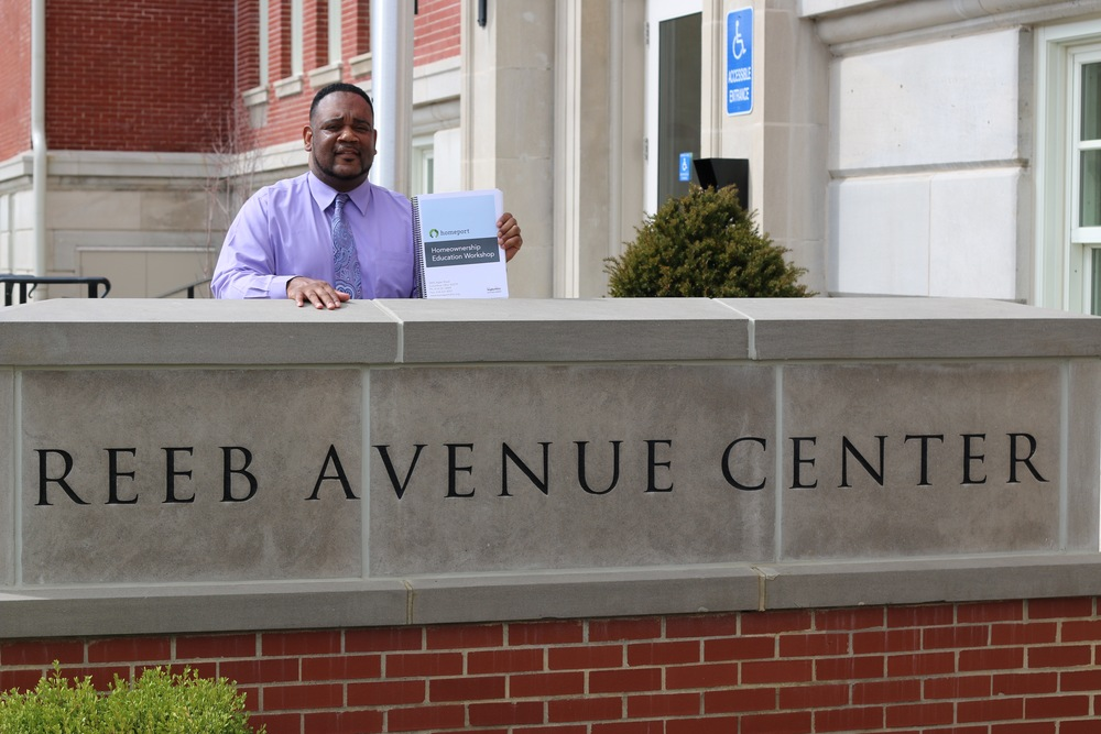 Homeport Housing Advisor Kerrick Jackson holds up book he will provide at classes