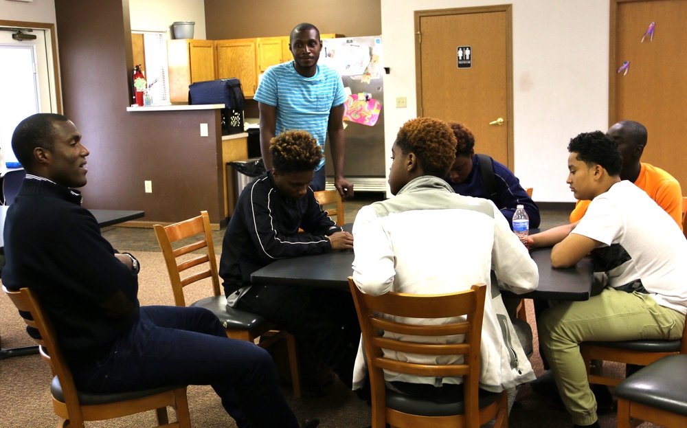 Mark, center, looks on at Marsh Run Apartments while special guest George Foreman III, left, speaks to teens.