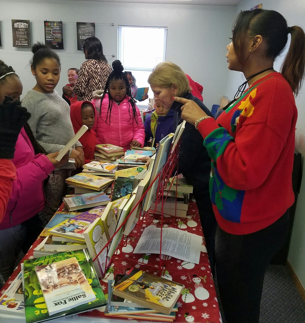 Homeport Board Chair Chris Hune, second from right, helps children select books at Georges Creek book fair event.