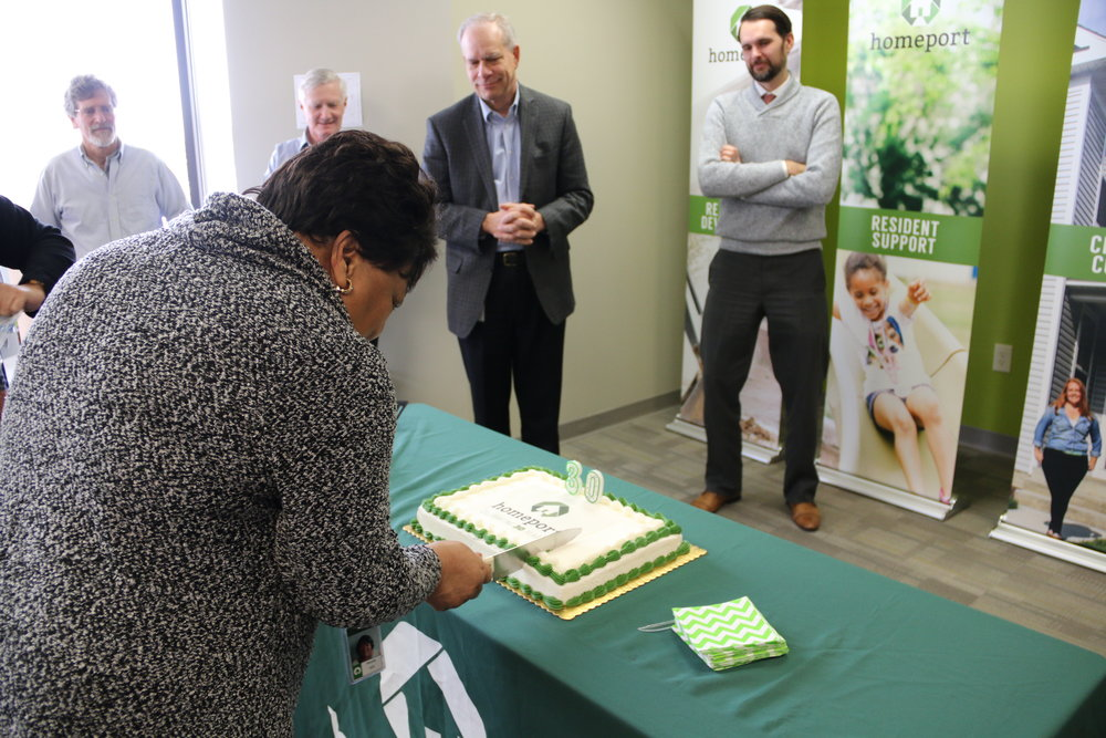 Homeport Vice President Maude Hill slices 30th anniversary cake. Homeport President & CEO Bruce Luecke, second from right, watches.