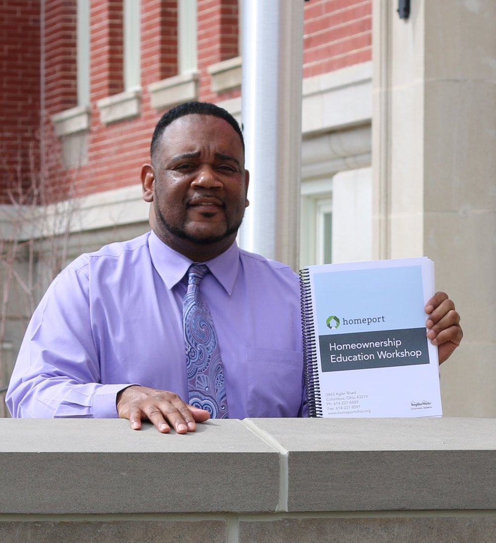 K errick Jackson, Homeport Housing Counselor, with instructional book used in classes.