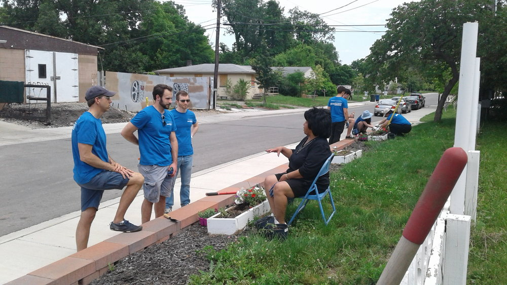 Chase employees and Marie Moreland-Short on the edge of the American Addition community garden.