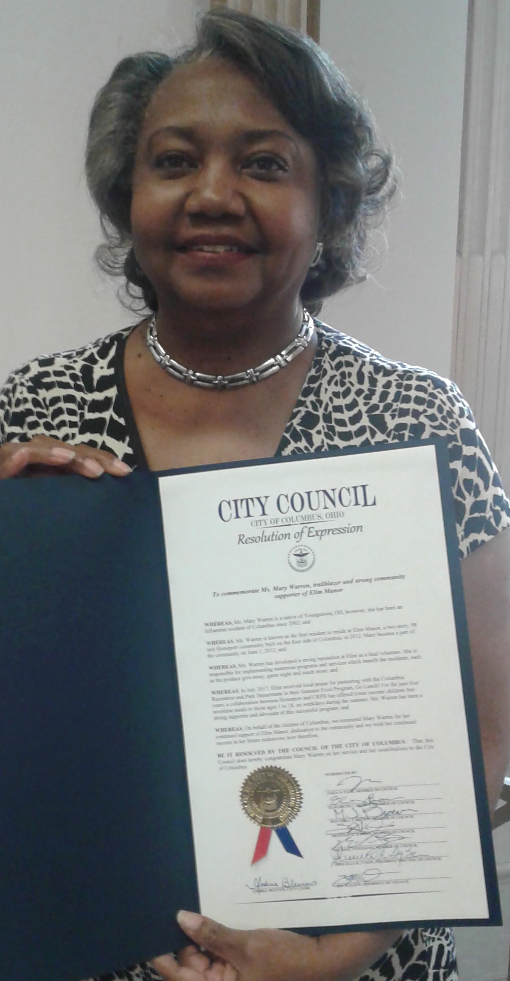 Mary Warren holds resolution honoring her efforts.