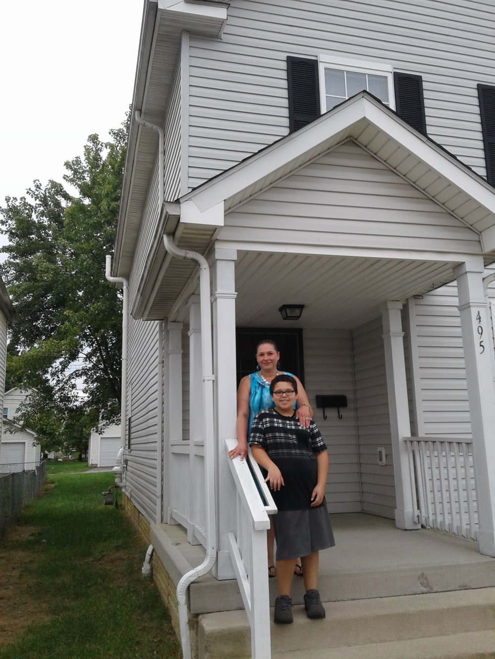 Maggie Parks and son Bryan on steps outside their new home.