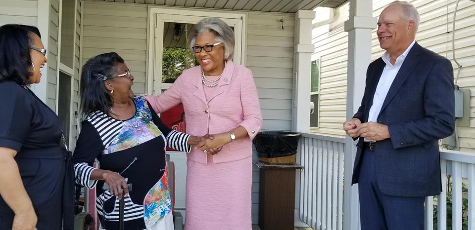 Joyce Mayne, second from left, accepts a congratulatory handshake on her front porch from U.S. Rep. Joyce Beatty. On right is Homeport President & CEO Bruce Luecke. On left is Homeport Lease Option Program Manager Brenda Moncrief.
