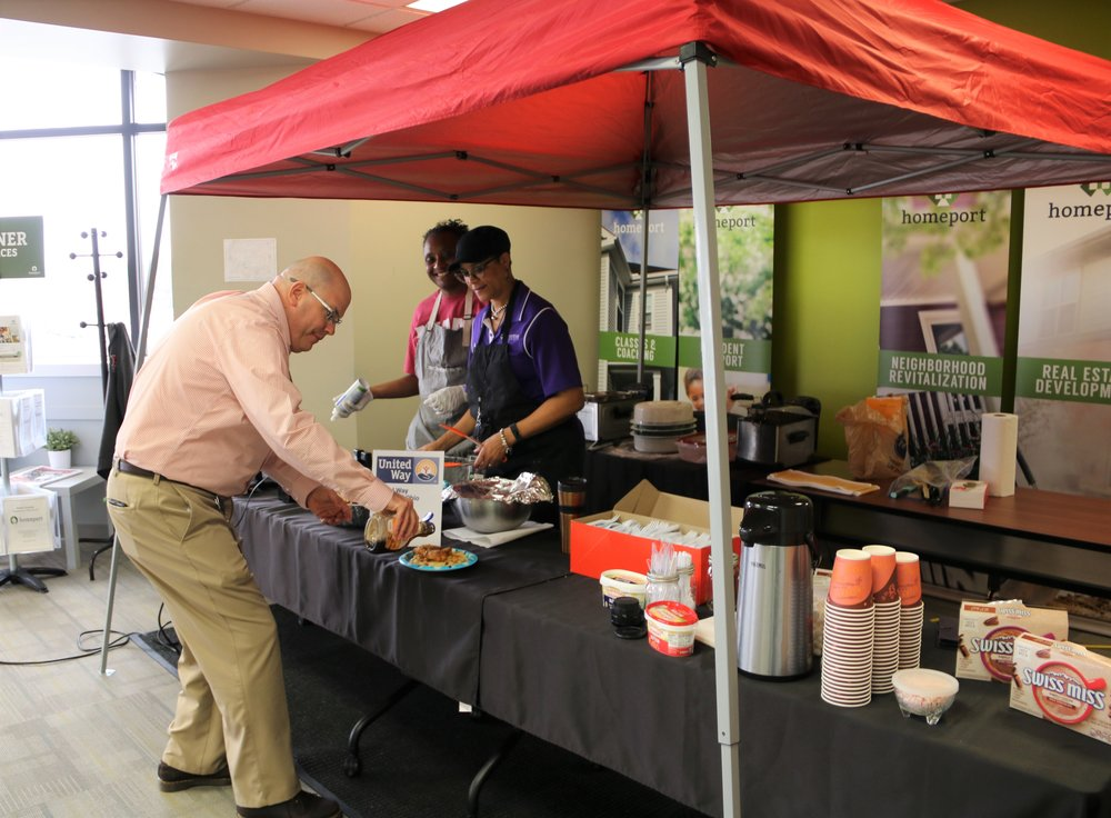 """Marketing and Brand Promotion Director Ray George pours on support — and syrup — for a Homeport fund-raiser for United Way of Central Ohio. The """"tailgate"""" style event, featuring chicken and waffles and cookout meats, was organized by senior staff members Netta Whitman, left, and Laverne Price."""
