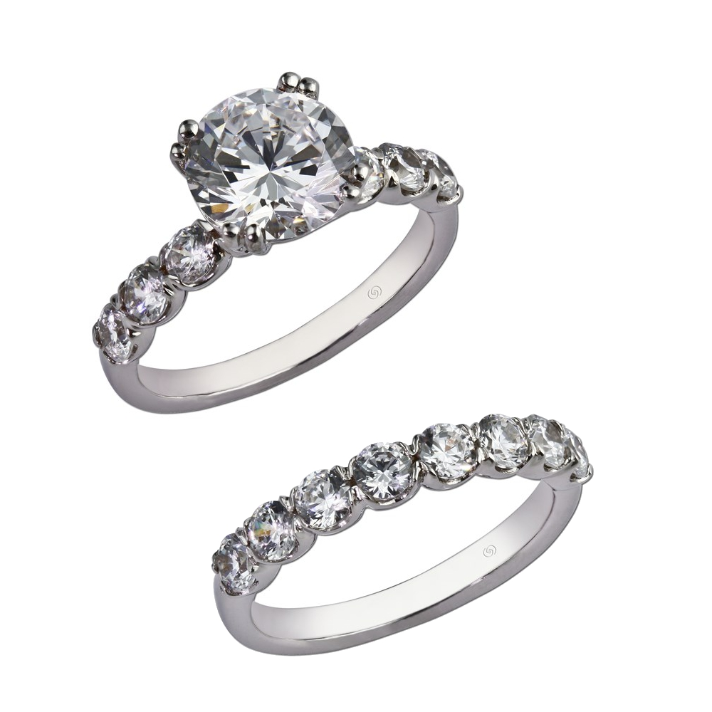 Engagement ring with three larger round diamonds, half bezel set, accentuating either side of a magnificent center stone.  With wedding band for bridal set. Style 28744