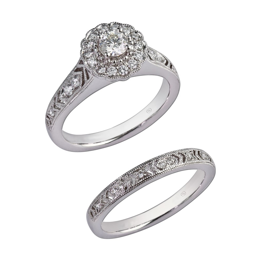 Just Beginning engagement setting with a hand crafted design along the shoulders and sparkling bead set diamonds.  A flower shaped diamond halo accentuates a beautiful diamond.  Scrollwork hand engraved in the gallery adds a romantic touch.  With wedding band for bridal set. Style 28976