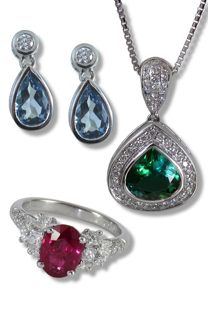 Colored gemstone jewelry cover.  Sapphire ring, spessartite garnet earrings with diamonds, and bi-color tourmaline pendant with diamonds.