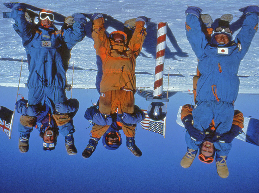 Trans-Antarctica Expedition team (Victor Boyarsky, Geoff Somers, Qin Dahe, Jean-Louis Etienne, Will Steger, Keizo Funatsu). Happy to have enough fuel to keep the expedition going, they play with the camera at the bottom of the world. December 11, 1989. Photo ©Will Steger.