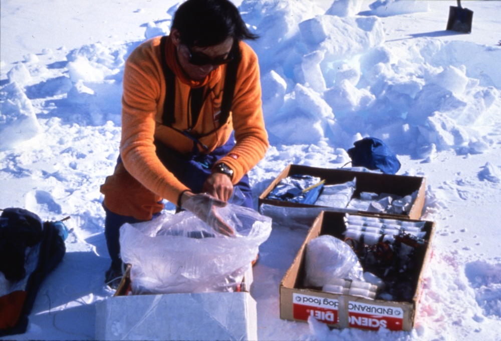 Dahe carefully packs his collected snow samples in empty dog food boxes. Photo ©Will Steger.
