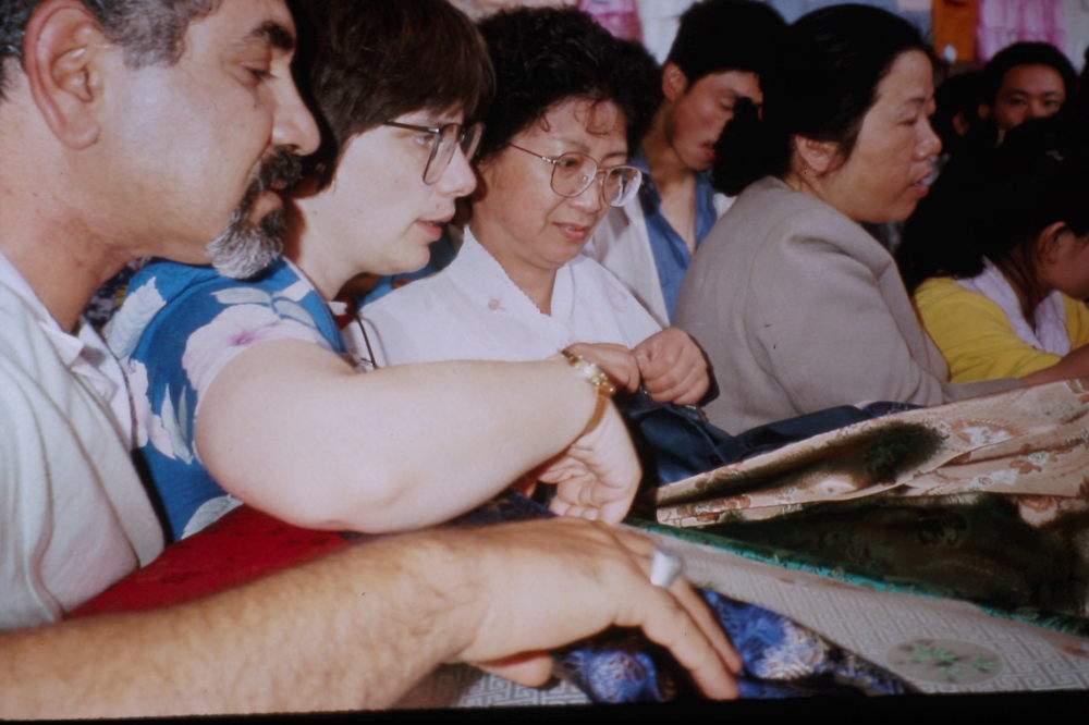 Zhou Qinke (center) helps Mustafa Moammer (left) and Cathy de Moll buy silk in an open Lanzhou market, May 1990. Photo: Cynthia Mueller