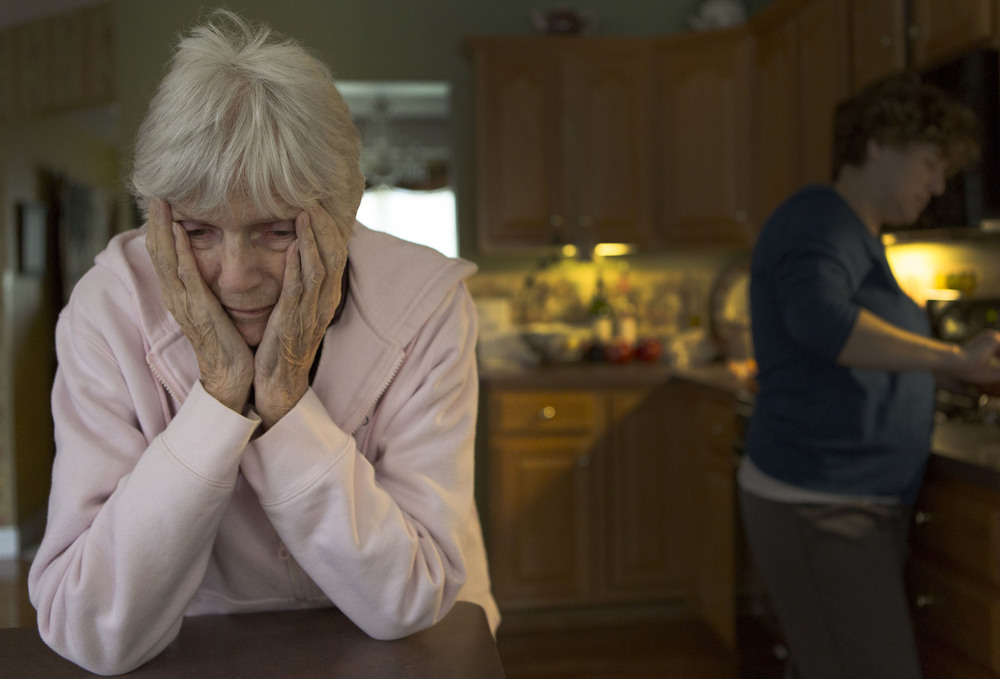 Nancy Davis holds her head in confusion in her home in Greece, N.Y. while her caretaker Vicki Hunt prepares her lunch on Oct. 16 2016.