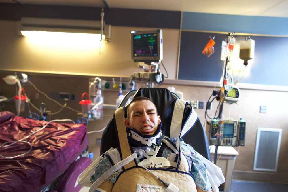 Chris, still unaware, struggles in his chair at Strong Memorial Hospital. Nurses move comatose patients from the bed to the chair one to two times gives them a better chance to wake up.