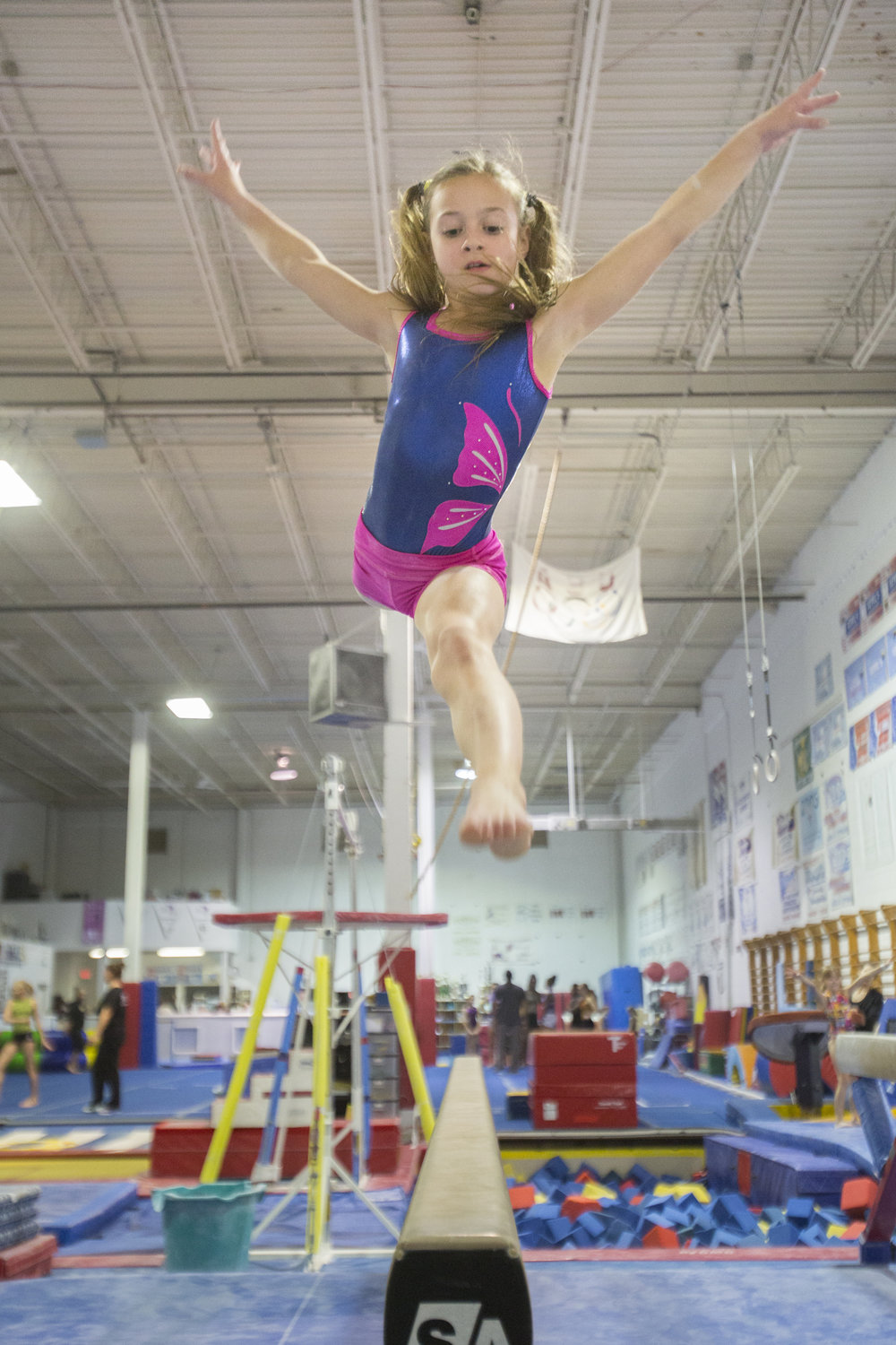 Maddie Maas leaps on the beam as she performs her routine during practice at Bright Raven Gymnastics Company in Rochester, N.Y. Oct. 28, 2014.
