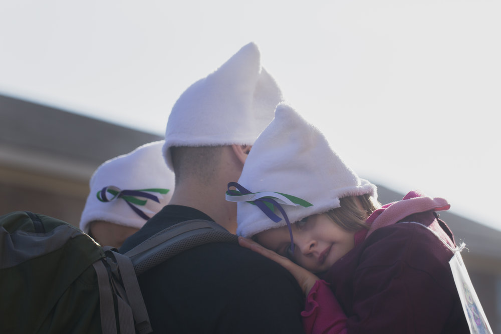 Bernadette Hanlon rests her head on her father Ryan Hanlon's shoulder during the Women March held at the Women's Rights National Historical Park in Seneca Falls, N.Y on Jan. 21, 2017.