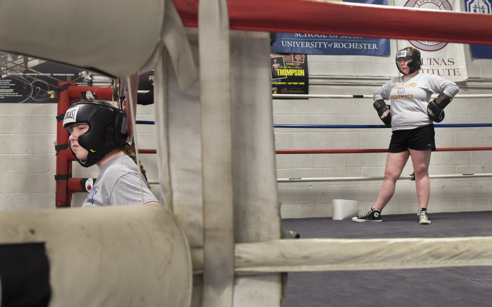 "Sarah Burke (left) sits on the sidelines while her opponent, Erin Ingalls (right), waits for her in the ring during practice at ROC Boxing in Rochester, N.Y. on Jan. 30, 2017. ""She hit me way too hard way too many times last week,"" said Burke, ""I refuse to spar with her."""
