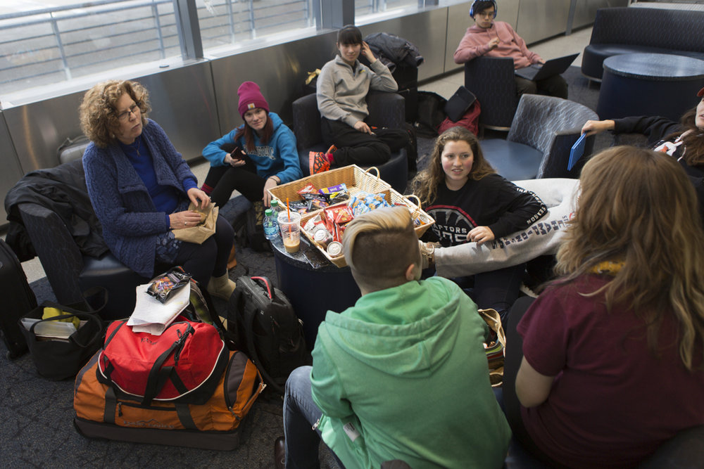 Professor Angela Kelly and members of the class enjoy the free snacks offered by the airline while waiting for the news about our flight.