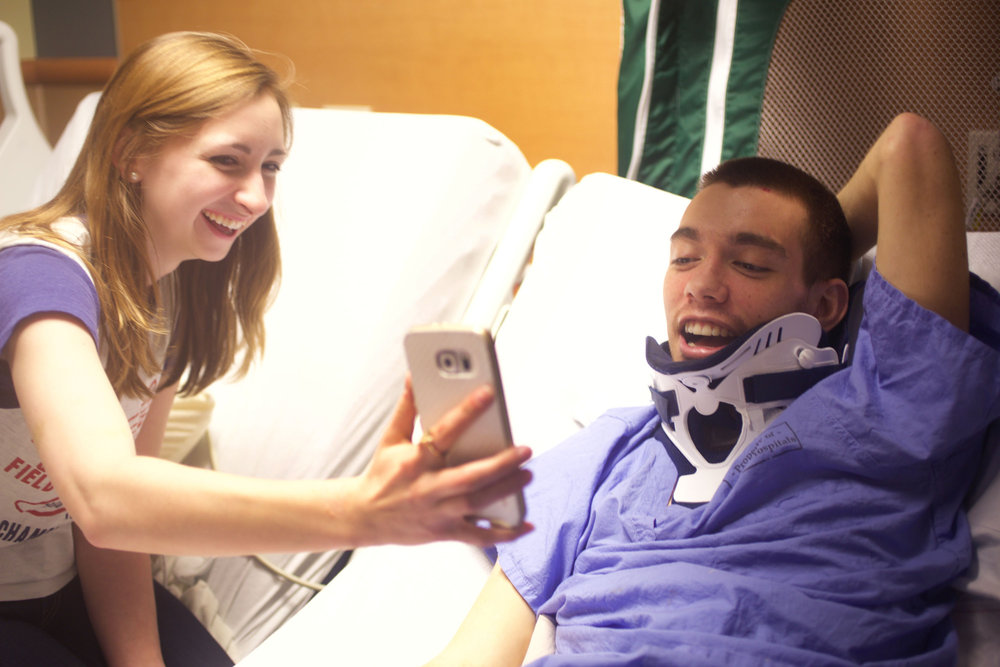 Chris's friend Marisa Langlois holds a cell phone up for Chris so that he can skype his extended family. Chris's mother Sarah, scheduled Chris skype sessions with his family every night though his recovery.