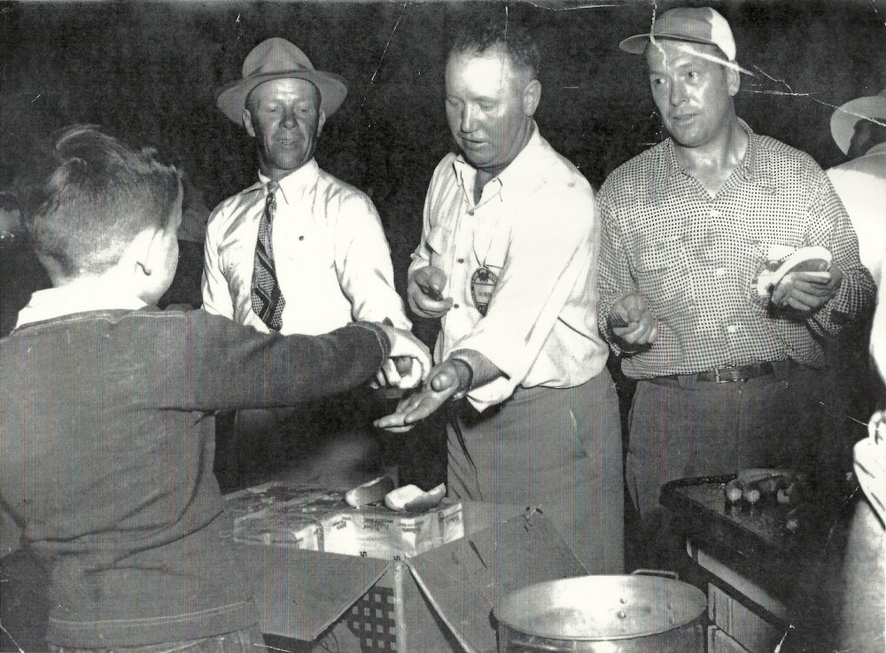 Boy serving hot dogs at an unknown event.