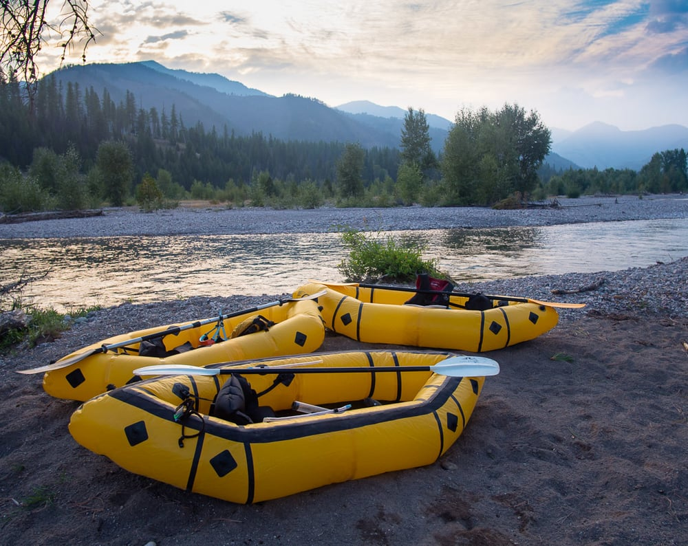 Packrafts and paddles wait next to the waters of the Flathead River - Photo: Colin Arisman