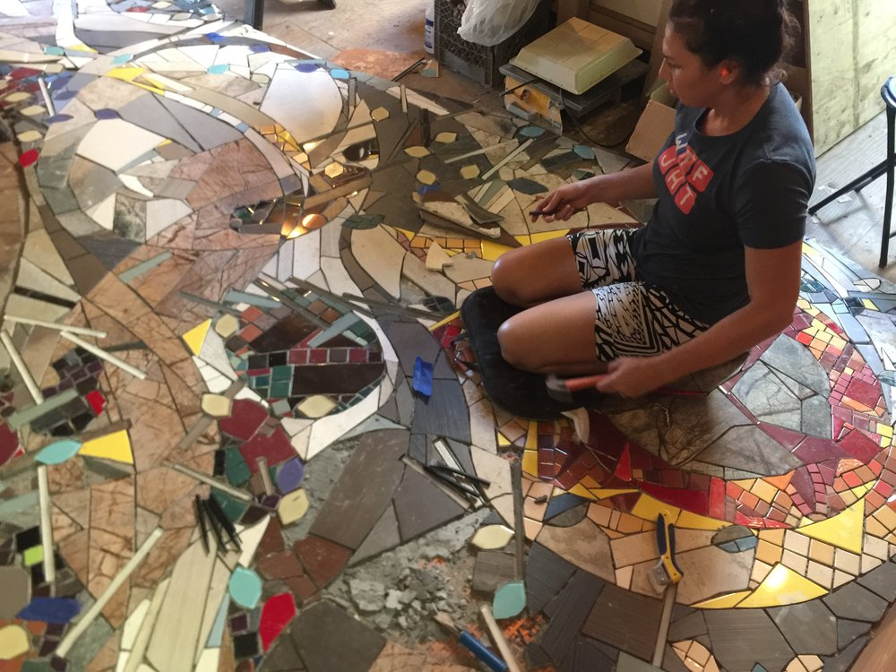 Above: Maya fills in remaining pieces of this biophilic floor mural which suggests fallen leaves and sticks strewn across a trail, cutting thru the living space.    The dull flicker of flames emanating from the fire place that will be installed later where she is sitting, draw the eye to intentional sprinkles of yellow fallen across the floor.
