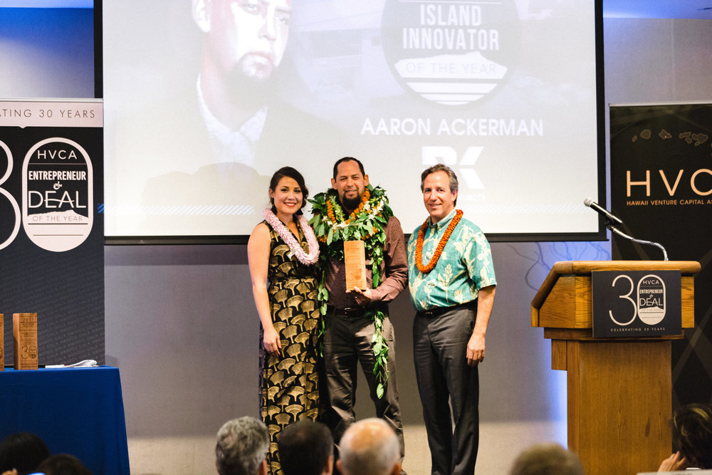 Meli James (HVCA President) and Rich Wacker (American Savings Bank President and CEO) present the 2017 Island Innovator award to Aaron Ackerman of Bowers+Kubota on March 1st, 2018 at the Waialae Country Club.